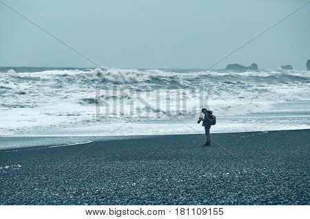 People walks and photographing on Reynishverfisvegur, Reynisfjara black sand beach with rocks, ocean and dark rain and storm clouds near the village of Vik in Iceland.