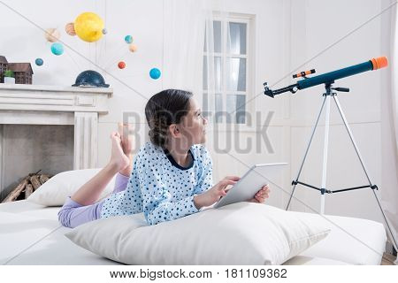 Cute Girl In Pajamas Lying On Bed With Digital Tablet And Looking At Telescope
