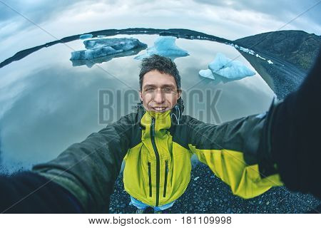 tourist make selfie on Glacial lagoon in Iceland in the fall. Cloudy foggy weather, mountains on the horizon.
