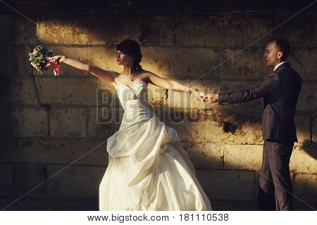 Bride Reaches Her Hand With A Bouqet To The Sun Standing Behind A Groom