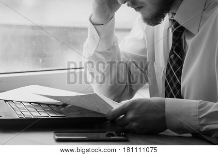 Young businessman sitting behind crumpled paper expectations Emotion