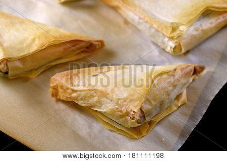Close-up on a batch of baked greek spanakopita