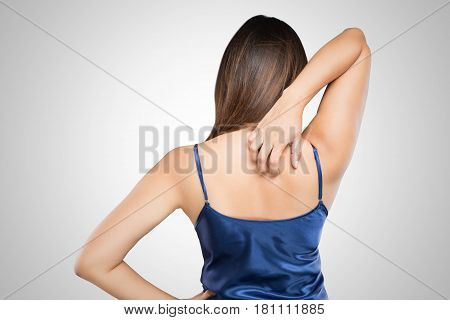 Woman scratching her itchy back with allergy rash Shoulder Concept with Healthcare And Medicine.
