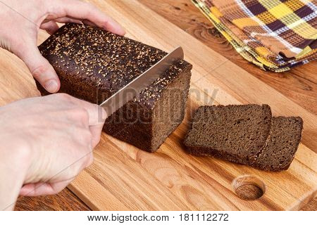 Cutting delicious homemade black bread. Borodinsky bread is a traditional Russian rye-wheat bread with maltose syrup malt and coriander