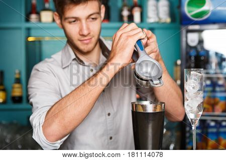 Barman in bar making alcohol cocktail. Professional bartender squeezing lime into mixing glass for citrus drink. Party time in night club
