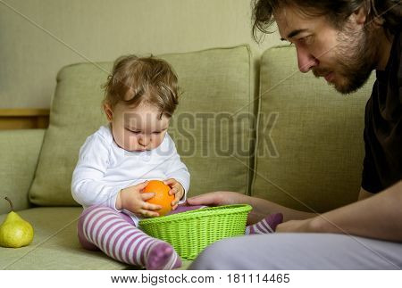 Cute baby girl plays with fruits with her father at home. The one-year child holds an orange in hand.