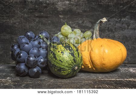 Pumpkins and fresh red and white grapes on wooden table.