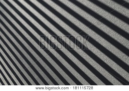 Parallel diagonal black and white shadow lines on asphalt.
