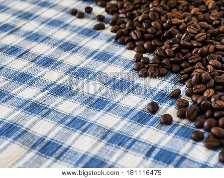Scattered roasted coffee grains over blue and white square fabric from top view