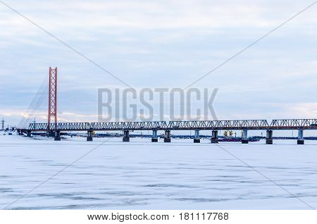 Cable-stayed bridge with one pylon tower across Ob river in Siberia. Railroad bridge in front. Winter period.