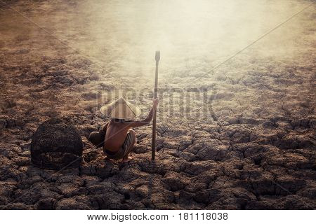 Asian sad a boy sitting on dry ground .concept hope and drought