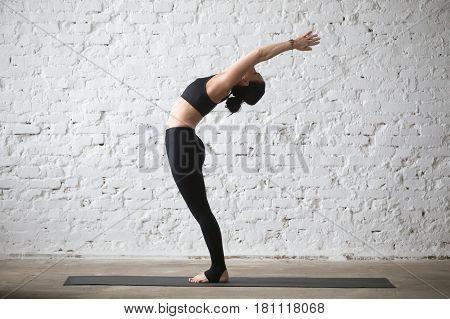 Young yogi attractive woman practicing yoga concept, stretching in Ardha Chakrasana exercise, Standing Backward Bend pose, working out, wearing black sportswear, full length, white loft background