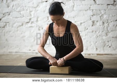 Young yogi attractive sporty woman practicing yoga concept, doing Butterfly exercise, baddha konasana pose using block, working out wearing black sportswear pants, full length, white loft background