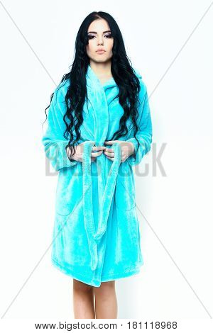 pretty serious cute sexy girl or beautiful woman with fashion makeup and curly long hair posing in turquoise velour bathrobe isolated on white background