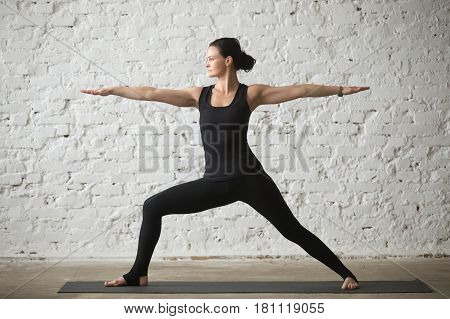 Young yogi attractive woman practicing yoga concept, standing in Warrior Two exercise, Virabhadrasana II pose, working out, wearing sportswear, black tank top and pants, full length, white loft