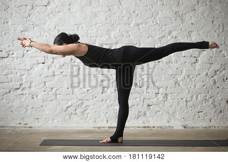 Young yogi attractive woman practicing yoga concept, standing in Warrior three exercise, Virabhadrasana III pose, working out, wearing sportswear, black pants, full length, white loft background