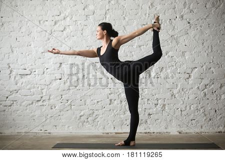 Young yogi attractive woman practicing yoga concept, standing in Natarajasana exercise, Lord of the Dance pose, working out, wearing sportswear, black tank top and pants, full length, white background