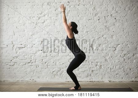 Young yogi attractive woman practicing yoga concept, standing in Utkatasana exercise, Chair pose, working out, wearing sportswear, black tank top and pants, full length, white loft background