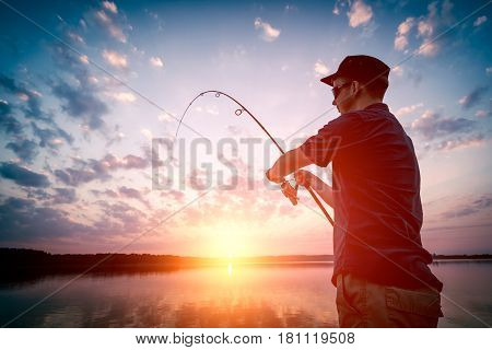 Man fishing at sunset. Hobbies performed in free time.