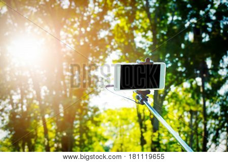 selfie stick over nature forest background which conveys the concepts of traveling,vacation and holidays