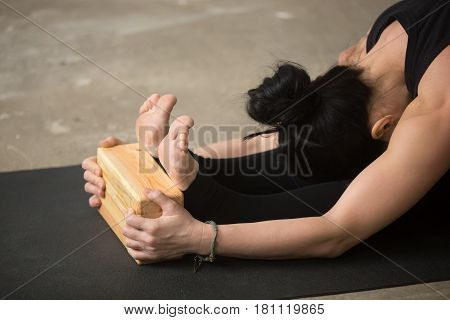 Young attractive sporty yogi woman practicing yoga concept, sitting in paschimottanasana exercise, using wooden block, seated forward bend pose, working out, close up of legs and hands with brick