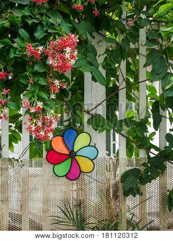 Colorful pinwheel on white fence with blooming nice flowers