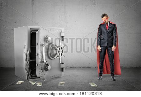 A sad businessman in a red cape and a mask standing beside a broken strongbox with dollar bills lying around. Safekeeping and loss. Theft. Investment and insurance.