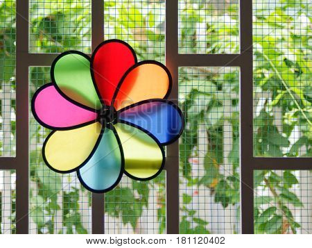 Colorful pinwheel on window with bright nature background