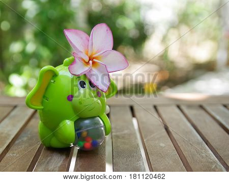 Elephant toy with a blooming plumeria flower on her ear on a wooden table in the garden with bright nature bokeh in the background.