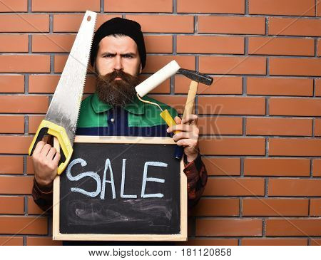 Bearded Worker Holding Various Building Tools And Board, Serious Face