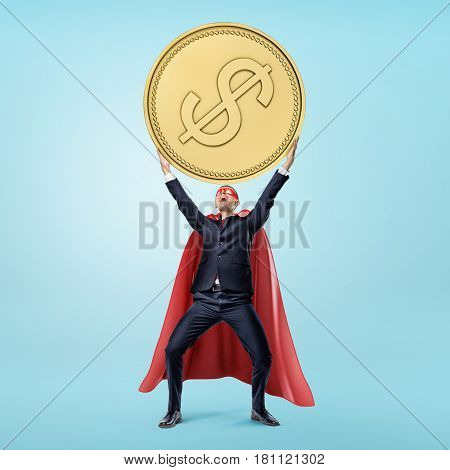 A businessman in a red flowing cape and a mask holding a huge golden coin in his hands in victory motion. Business rewards. Financial wisdom. Winning big.
