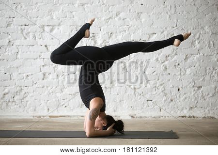 Young yogi attractive woman practicing yoga concept, doing variation of supported headstand exercise with bent legs, salamba sirsasana pose, working out wearing black sportswear, white loft background