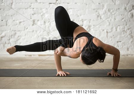 Young cool yogi attractive woman practicing yoga concept, standing in Dragonfly exercise, Maksikanagasana, Parivrtta Eka Pada Danda Koundiniasana pose, working out, full length, white loft background
