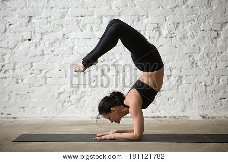 Mid aged yogi attractive woman practicing yoga concept, standing in vrischikasana exercise, Scorpion pose, working out, wearing sportswear, black tank top and pants, full length, white loft background