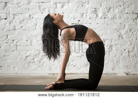 Middle aged smiling yogi woman practicing yoga concept, stretching in Ustrasana exercise, Camel pose, working out, wearing sportswear, black tank top and pants, full length, white loft background