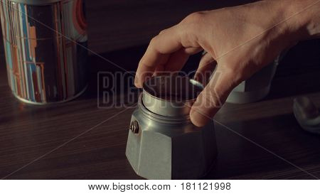 Close up of man's hand opening coffee geyser