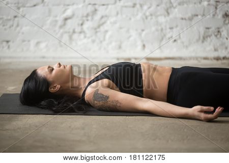 Middle aged yogi woman practicing yoga concept, lying on floor in Savasana exercise, Corpse, Dead Body pose, working out, wearing sportswear, black top and pants, close up, white loft background