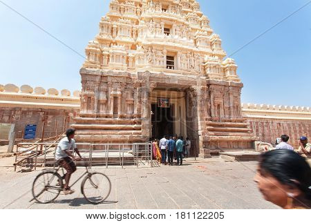 SRIRANGAPATNA, INDIA - FEB 18, 2017: Cyclist driving past the 10th century Ranganathaswamy temple with carved gate gopuram on February 18, 2017. Population of Karnataka is 62000000 people