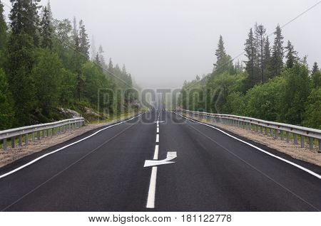 Trunk asphalt road among the hills and forests in the fog