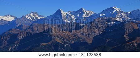 Famous mountain range Eiger Monch and Jungfrau on a clear autumn day. View from mount Niesen Bernese Oberland.