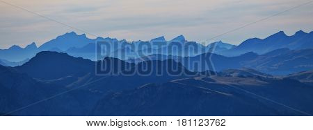 Blue mountains. Silhouettes of mountains in the Swiss Alps. View from mount Niesen. Autumn evening.