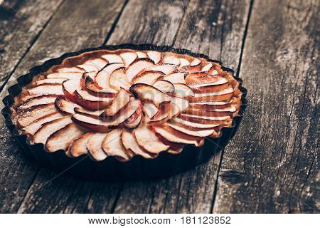 Apple pie tart on rustic wooden background. Ingredients - apples and cinnamon .Top view.