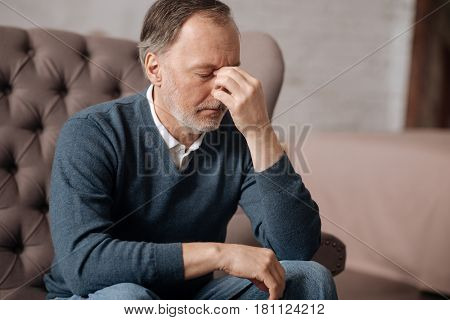 Sick headache. Portrait of old man touching nasal bridge with fingers while having terrible headache.