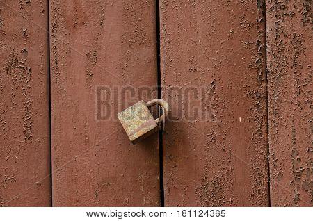 The lock locks the brown wooden door. The paint on the door is partially damaged.