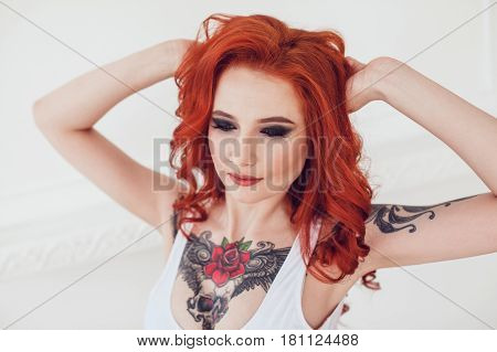 Portrait of a beautiful sexy girl with red hair and a tattoo. Woman with make-up and curls.