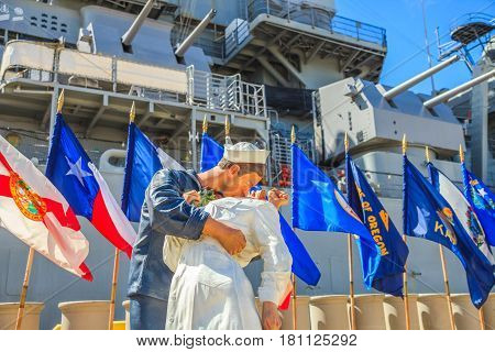 HONOLULU, OAHU, HAWAII, USA - AUGUST 21, 2016: victory kiss statue at battleship Missouri Memorial with flags at Pearl Harbor. Sailor and nurse in NY Times Square 1945 for Japan surrendered war end.