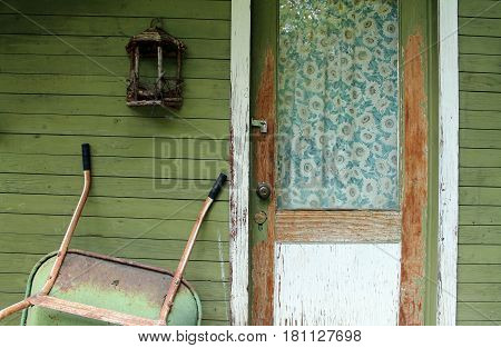 Weathered Front Door with Vintage Curtains on a Green Wooden Farmhouse