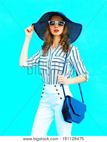 Fashion Portrait Young Woman Wearing A Straw Hat, White Pants And Handbag Clutch Over Colorful Blue