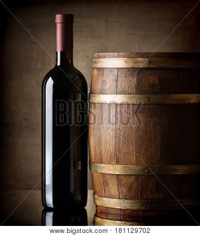 Bottle of red wine and a wooden barrel