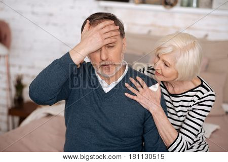 I am sick. Senior man feeling bad and touching his forehead while his wife is trying to support him.